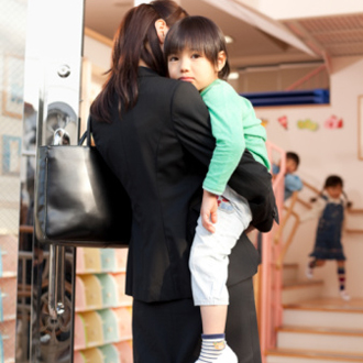 Mother in business suit taking child into school