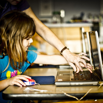 Instructor assisting child at computer workstation
