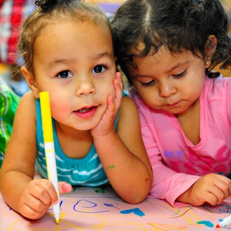2 children coloring with markers