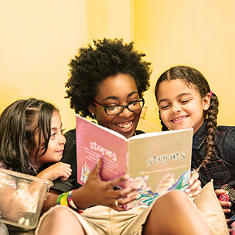 Teacher reading to two girls