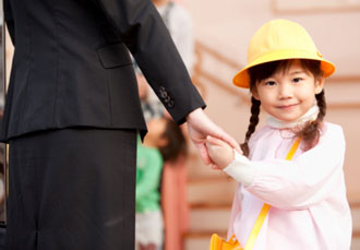 child in a yellow construction hat, holding adult's hand