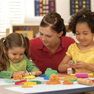 Teacher with kids on either side, playing with play dough