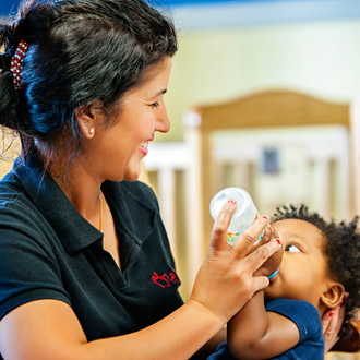Child care provider feeding an infant