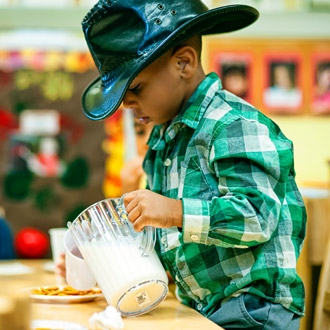 A boy wearing cowboy hat pouring milk