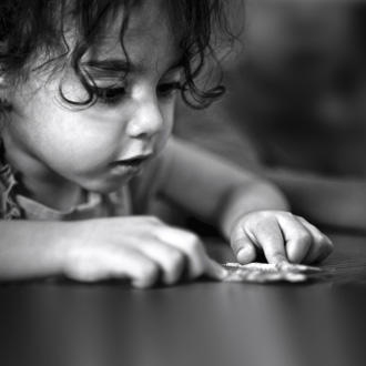 Curly hair girl playing with paper on table
