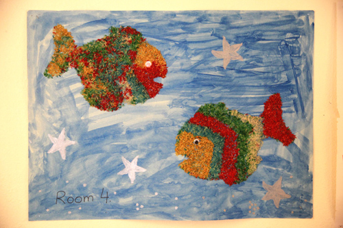 Colorful paper mache fish on a blue background with stars