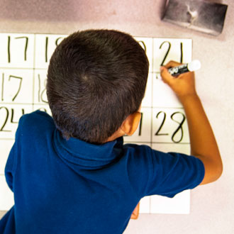 Kid writing numbers on the wall