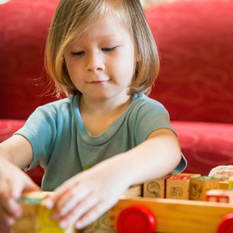 Child playing with blocks in front of the red couch