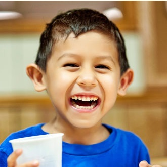Smiling boy holding cup