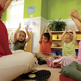 Grupo de niños sentado en el piso con las manos alzadas