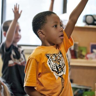 Niño afroamericano levantando la mano