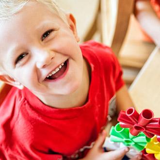 Niño sonriente con un juguete en la mano