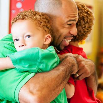 Padre abrazando a sus hijos