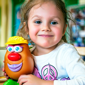 A smiling girl holding a toy