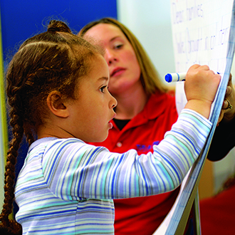 Teacher with girl drawing