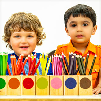Two boys behind colored pencil boxes